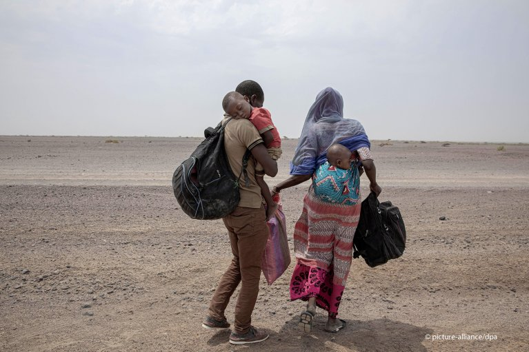 Fatma and her husband Yacoub, migrants from Mali, carry their children as they make their way in Lahj, Yemen | Photo: picture-alliance/AP Photo/Nariman El-Mofty