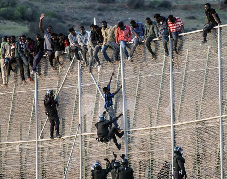 مهاجرون يعبرون السياج الحدودي لجيب مليلة الإسباني في المغرب. الصورة: أرشيف/رويترز