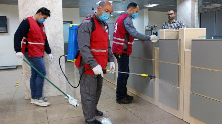 © رويترز |أعضاء في الهلال الأحمر الليبي يقومون بتعقيم أحد المكاتب الحكومية بمصراته (غرب)، 21 مارس/آذار 2020.