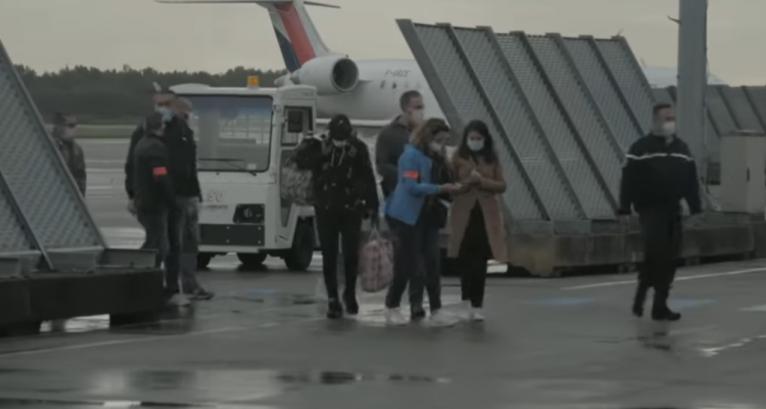 Ismail, au centre, est accompagné d'une quinzaine d'officiels et de policiers au moment de débarquer en France    Source : Capture d'écran Channel 4 News