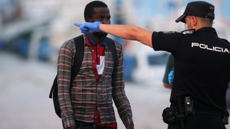 From file: A migrant and a Spanish police officer seen in Malaga, southern Spain, August 2018 | Photo: REUTERS/Jon Nazca