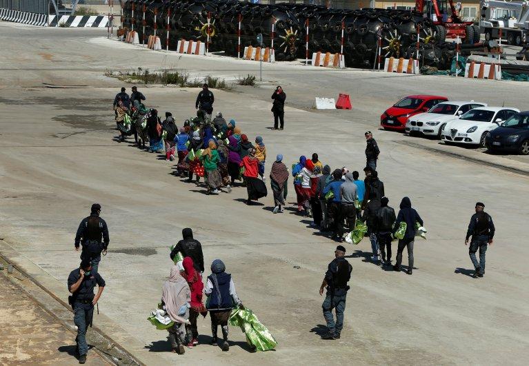 Des migrants sont escortés par des policiers après avoir débarqué en Sicile. Crédit : Reuters