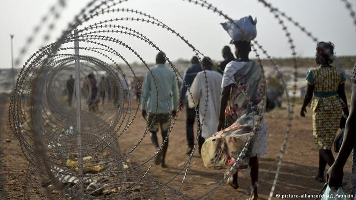 Südsudan Krise Menschen gehen entlang eines Stacheldrahtzauns (picture-alliance/dpa/J.Patinkin)