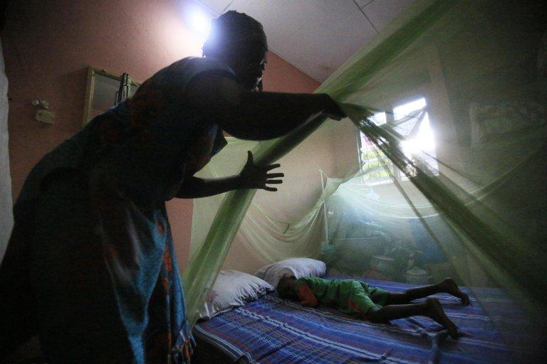 """ansa / امرأة تنصب ناموسية فوق سرير طفلها في أبيدجان بساحل العاج. المصدر: """"إي بي إيه""""/ ليجنان كولا."""