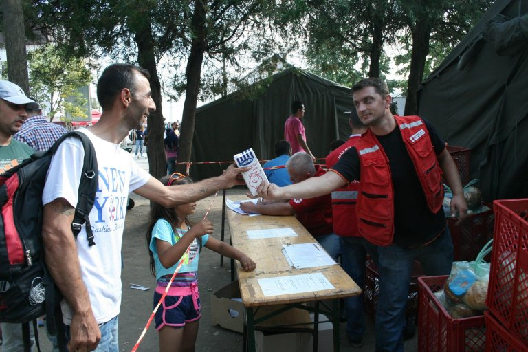A Red Cross of Serbia volunteer gives milk to a migrant for his child at the Presevo reception center, Serbia | Credit: Red Cross