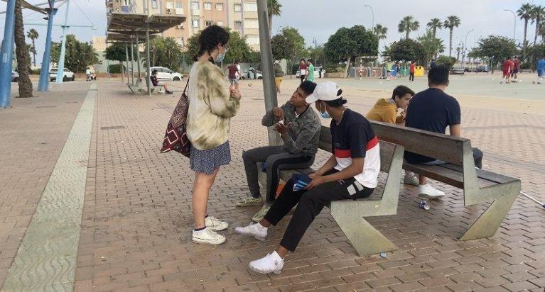شابان مغربيان يتناقشان مع عضوة في إحدى الجمعيات العاملة مع المهاجرين، في مليلة. المصدر: مهاجر نيوز