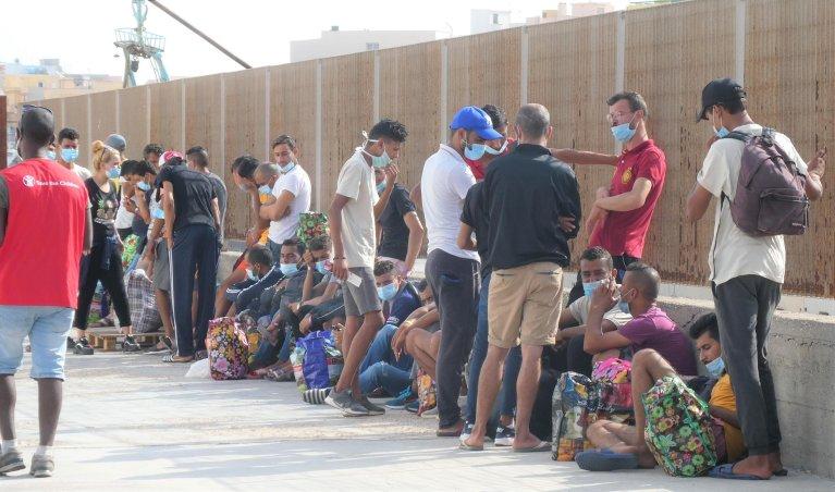 150 مهاجرا ينتظرون نقلهم بسفينة تجارية من لامبيدوزا إلى ميناء إمبديلكولي في صقلية، حيث سيتم نقلهم من هناك إلى سفينة الحجر الصحي. المصدر: أنسا / إيليو ديسيديريو.