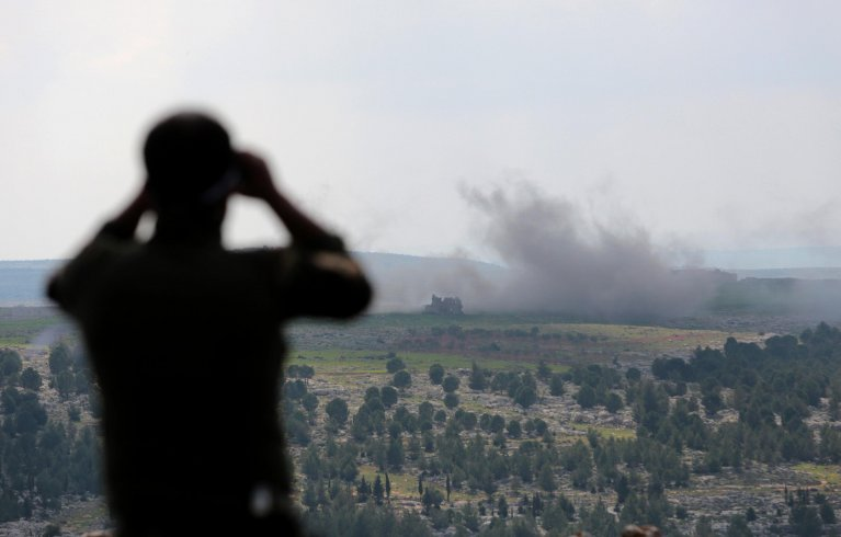 A soldier from the Free Syrian Army watches from the smoke rising from the village of Der Mismis in Afrion, Syria Credit: Epa