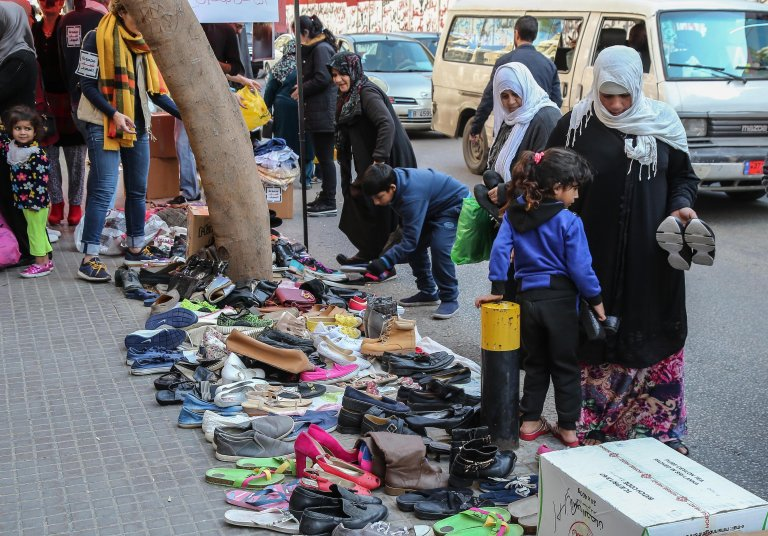 People check for clothes and shoes donated by citizens for poor families in front of the central bank in Beirut, Lebanon on July 7, 2020 | Photo: EPA/Nabil Mounzer