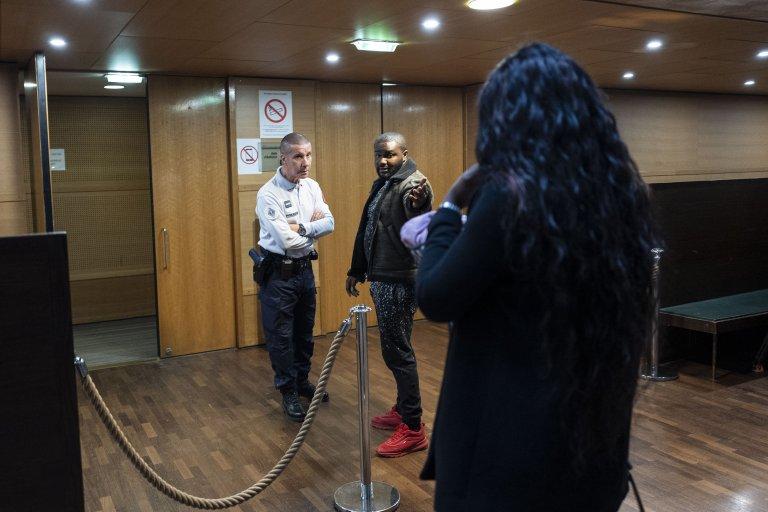 ROMAIN LAFABREGUE / AFP  Un policier (à g.) s'entretient avec un prévenu nigérian à l'extérieur de la salle d'audience avant le début du procès d'une affaire de réseau de prostitution à Lyon, le 6 novembre 2019.