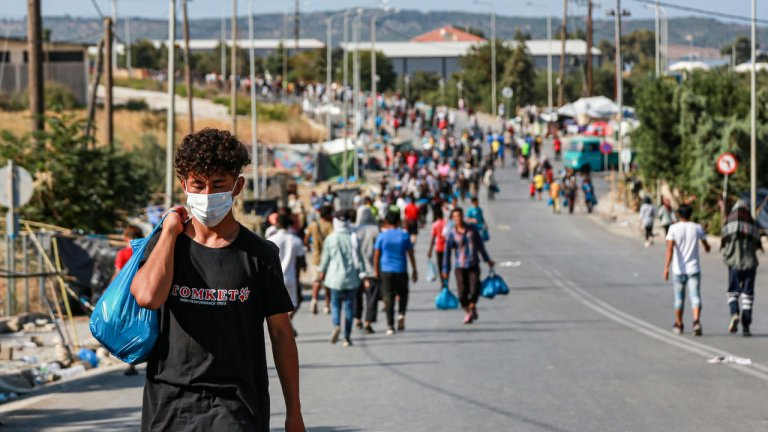 © أ ف ب |مهاجرون على طريق قرب مخيم موقت في جزيرة ليسبوس اليونانية في 17 ايلول/سبتمبر 2020.