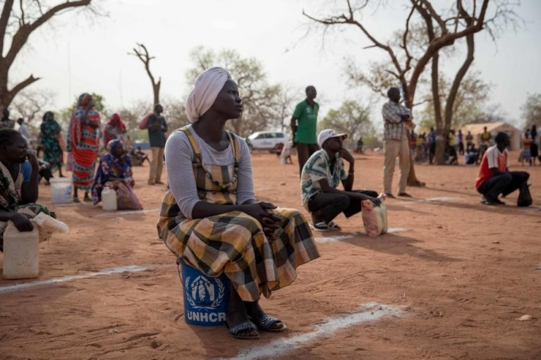 Des réfugiés soudanais se tiennent à distance les uns des autres lors d'une distribution de nourriture et de savon au camp d'Ajuong Thok au Soudan du Sud, en avril 2020.  Crédit : HCR / Elizabeth Marie Stuart