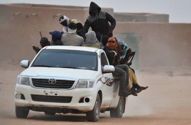 AFP/Issouf Sanogoissouf Sanogo |Une camionnette transportant des migrants passe à Agadez au Niger. Les passagers s'accrochent aux bâtons attachés au camion, à ne pas tomber en roulant dans le désert.