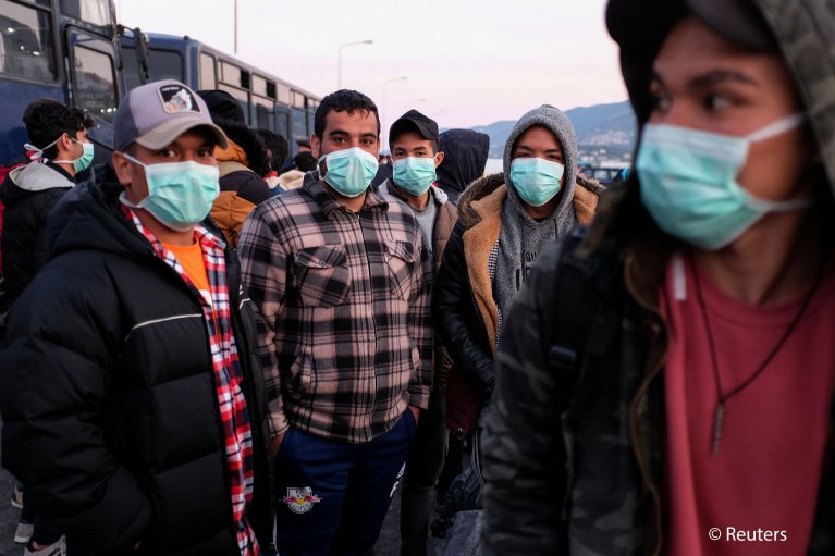 Migrants wearing protective face masks as a precaution against the spread of coronavirus disease (COVID-19), prepare to board a ferry that will transfer them to the mainland, at the port of Mytilene on the island of Lesbos, Greece, March 20, 2020 | Photo:  Reuters/Elias Marcou