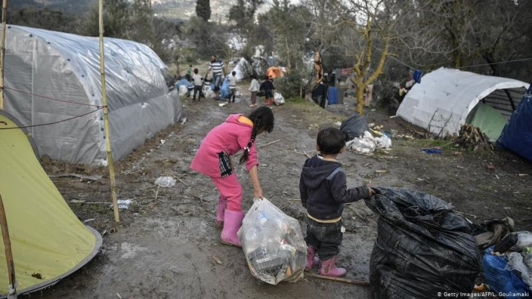 Migrant children help clear up rubbish at a refugee camp after a heavy bout of rain on the island of Chios in December | Photo: Getty Images/AFP/L. Gouliamaki