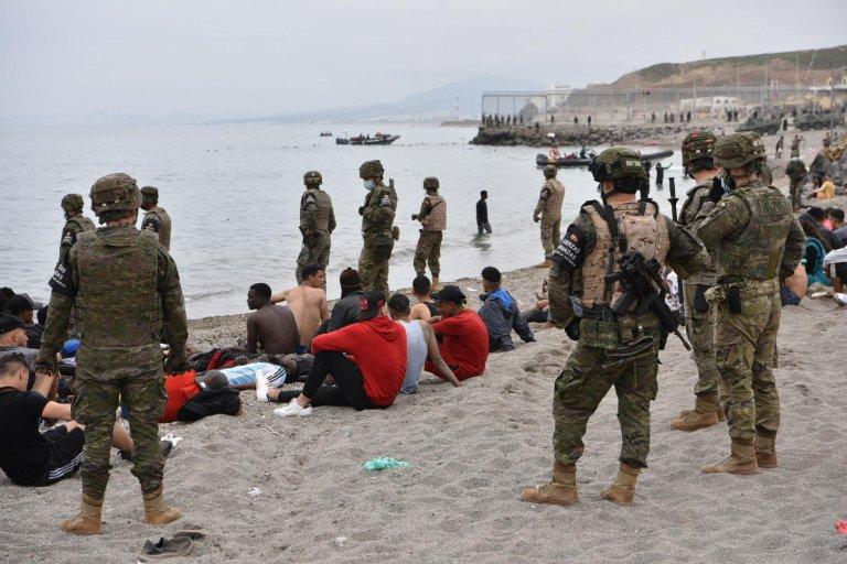© أ ف ب  المهاجرون الذين وصلوا سباحة إلى سبتة الإسبانية يستريحون بينما يقف الجنود الإسبان في الحراسة 18 مايو 2021 في سبتة.