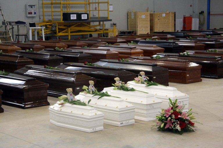 Coffins of victims in an hangar of Lampedusa airport on October 5, 2013 after a boat with migrants sank killing more than hundred people. Credit: ANSA/LANNINO