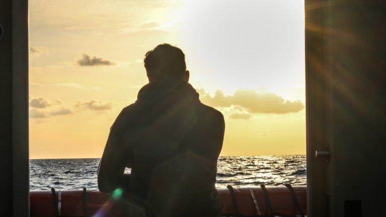 Un homme à bord de l'Ocean Viking regarde vers le large. Le navire humanitaire a été autorisé à débarquer les 39 migrants à son bord en Sicile le 20 janvier 2020. Crédit : MSF/Hannah Wallace Bowman