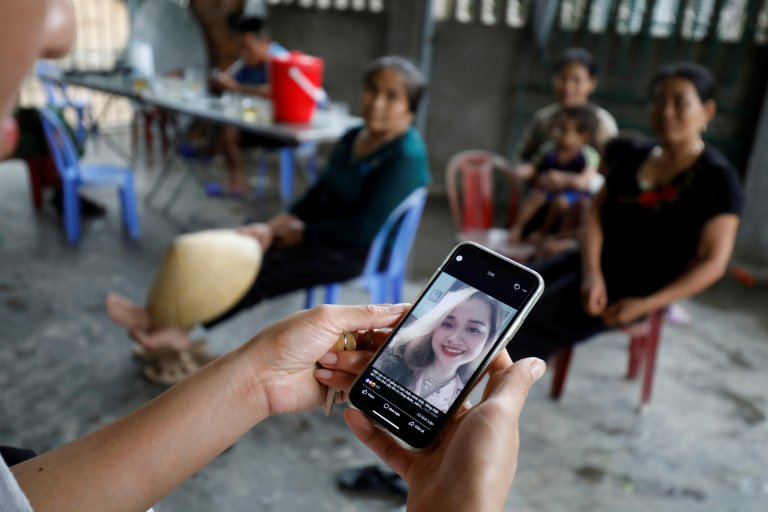 A relative looks at an image of Anna Bui Thi Nhung, a Vietnamese woman suspected to be among dead victims found in a truck in Britain | Photo: Reuters/Kham