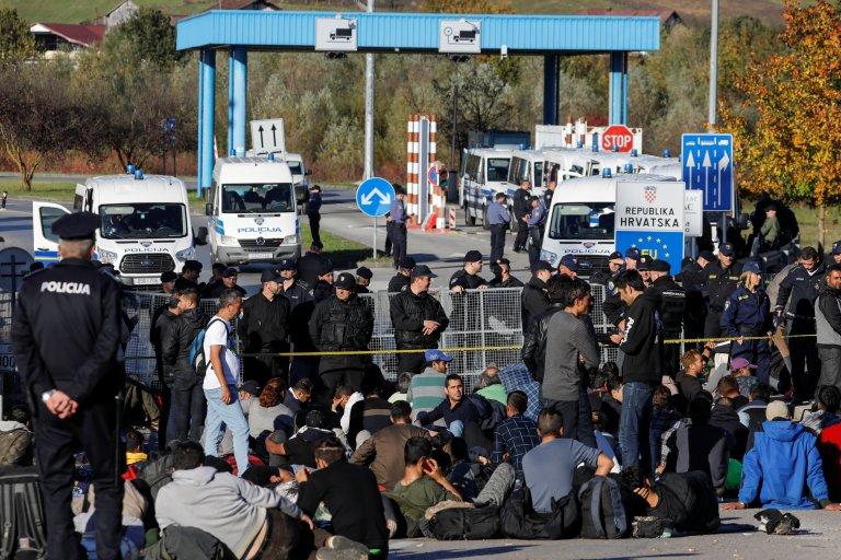 Des garde-frontières bosniens et croates face à des migrants, à Maljevac, le 24 octobre 2018. Crédit : Reuters