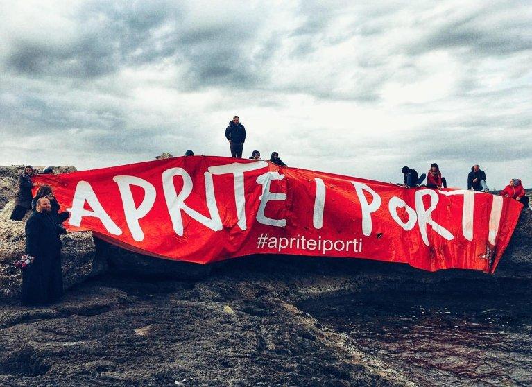 """احتجاج في لامبيدوزا، شارك فيه رجل الدين الأب """"كارميلو لا ماجرا"""" إلى يسار الصورة، وهو من الناشطين في الجزيرة، في يوم 19 آذار/ مارس الجاري. المصدر: أنسا."""