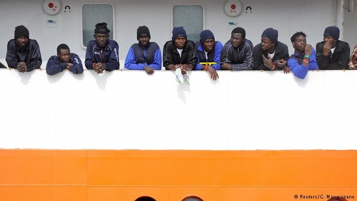 Migrants wait to disembark in Sicily
