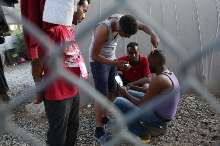 Refugees and asylum seekers cut their hair at the Moria camp on Lesbos, Greece   Credit: EPA/Orestis Panagiotou