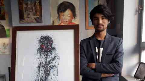 An Afghan artist standing next to a painting | Photo: Ali Rahimi